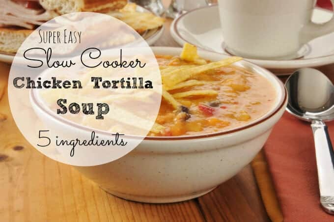A bowl of chicken tortilla soup with a sandwich in the background