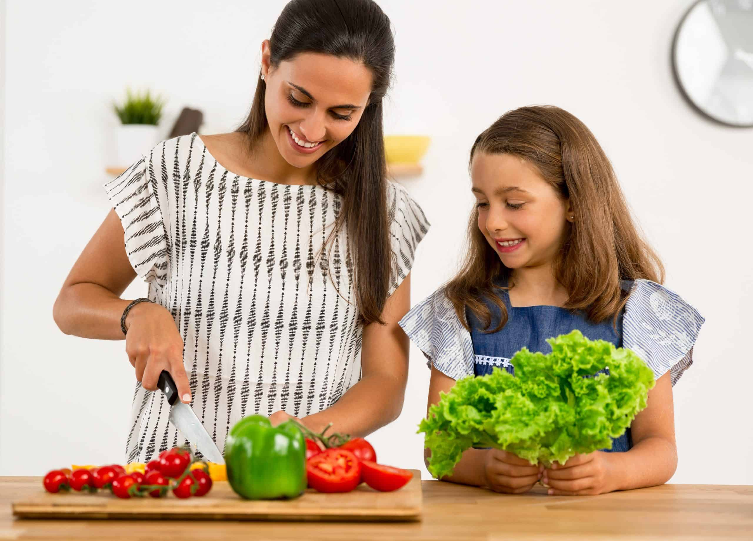 mom and daughter cutting vegetables